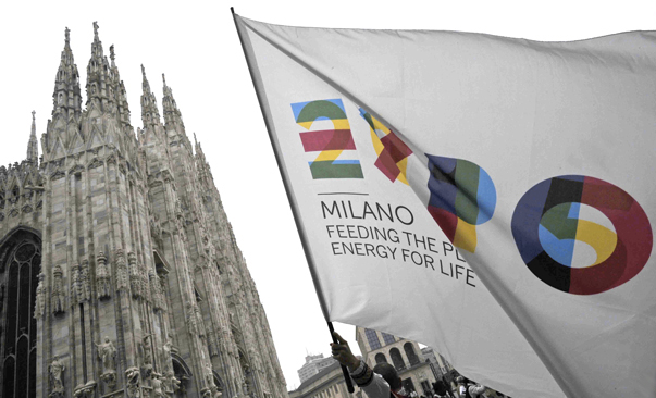 "Milan cathedral and in the foreground a flag of the Expo Milano 2015 with the inscription ""feeding the people, energy for life""."